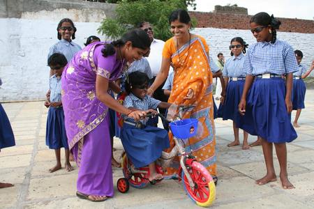 Schoolgirl with new tricycle 		                             copyright © Hamara Bandhan e.V.